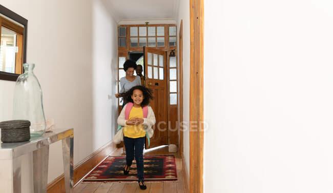 Vista frontal de una joven afroamericana que llega a casa y corre por el pasillo con una mochila y sonriendo, sus padres entrando por la puerta principal detrás de ella - foto de stock