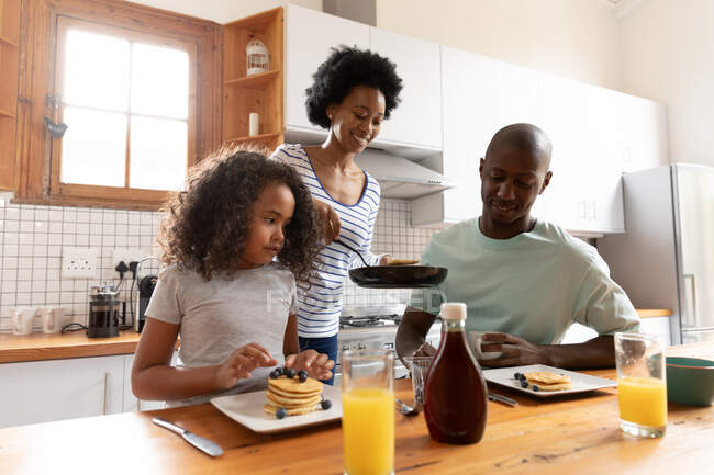 Front view of a young African American girl and her father at home in the kitchen in the morning, sitting at the kitchen island, the mother standing behind serving them pancakes from a frying pan — Stock Photo
