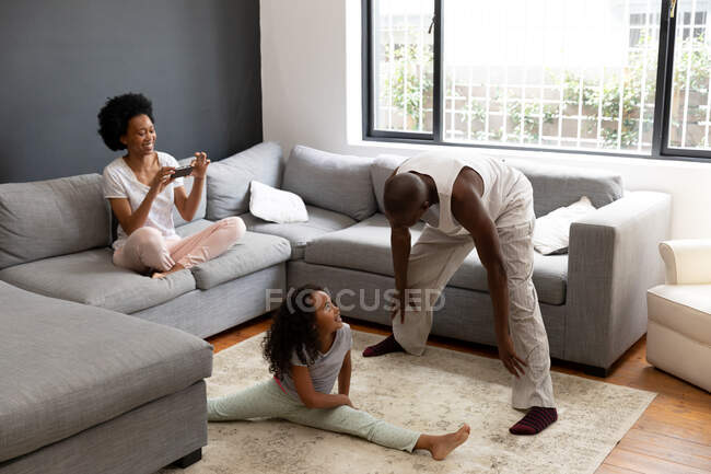 Front view of an African American couple and their young daughter relaxing in the living room together in the morning, the daughter sitting on the floor, her father standing talking to her and the mother sitting on the sofa — Stock Photo