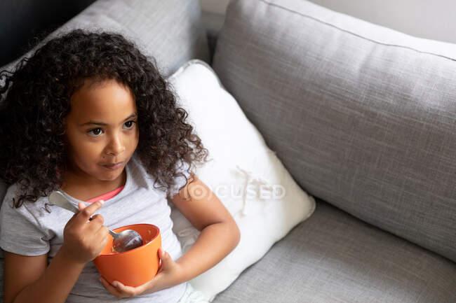 Vista ad alto angolo di una giovane ragazza afroamericana a casa in soggiorno, sdraiata su un divano che mangia una ciotola di cereali per la colazione — Foto stock