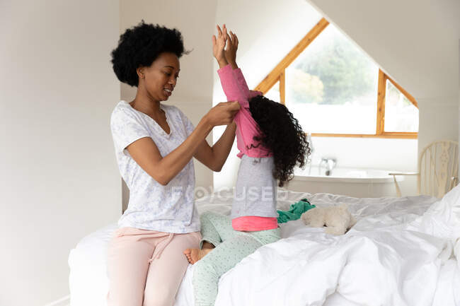 Side view of an African American woman in the bedroom with her young daughter, helping her to get dressed while sitting on the bed — Stock Photo