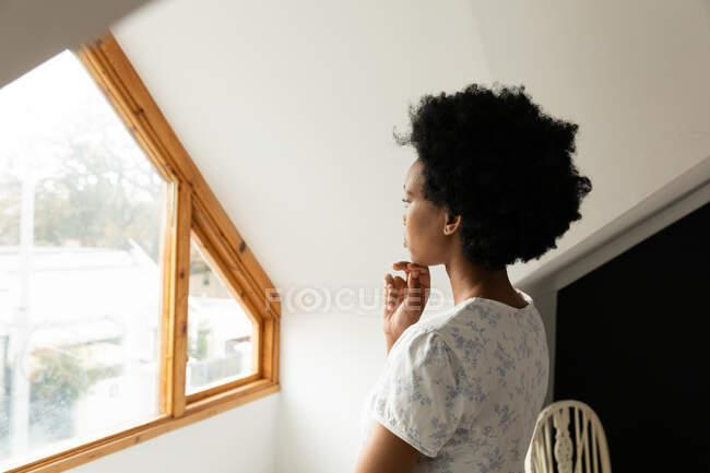 Vista laterale di una donna afroamericana in camera da letto, in piedi e guardando fuori dalla finestra — Foto stock