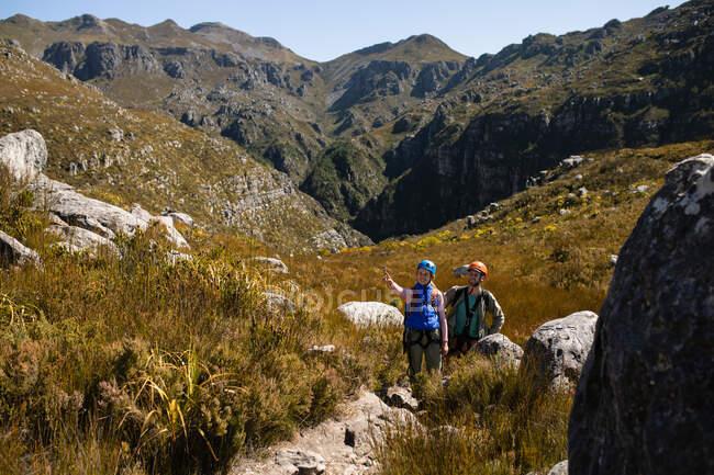 Vue de face du couple caucasien profitant du temps dans la nature ensemble, portant un équipement de tyrolienne, randonnée, la femme pointe du doigt par une journée ensoleillée dans les montagnes — Photo de stock