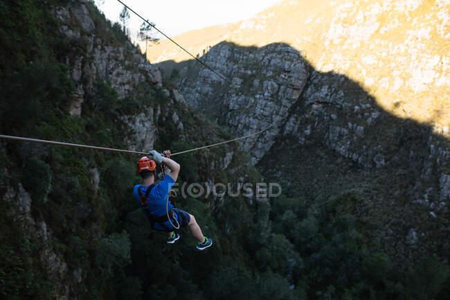 Vista posteriore ad alto angolo dell'uomo caucasico godendo del tempo nella natura, fodera zip in una giornata di sole in montagna. Divertente weekend di vacanza avventura. — Foto stock
