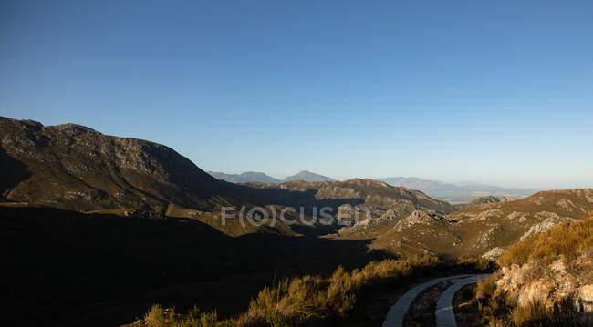 Atemberaubende Landschaft mit Bergen und Felsen in Feldern und Straßen zum Wandern an einem sonnigen Tag mit klarem blauen Himmel — Stockfoto