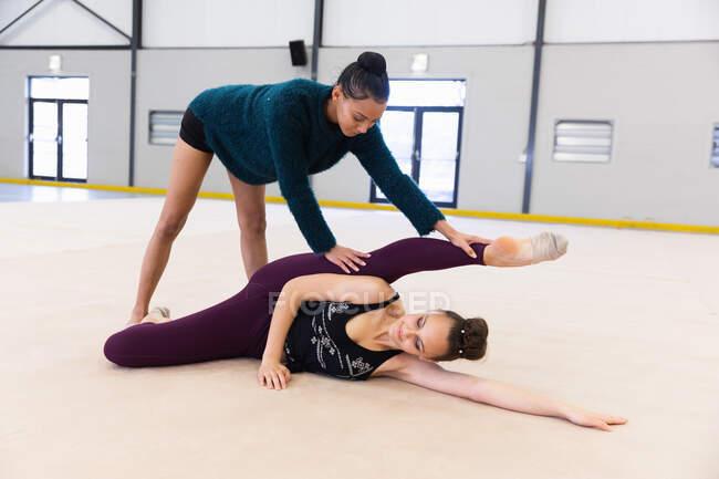 Вид спереди на подростков-кавказцев и гимнасток смешанной расы, практикующихся в спортзале вместе, одна девушка помогает другой размять ноги — стоковое фото
