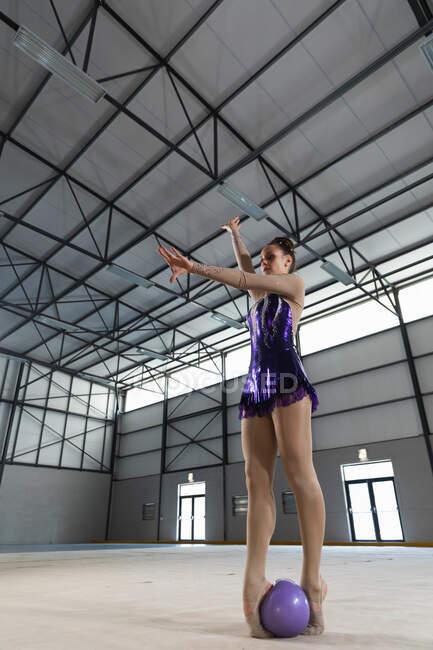 Baixo ângulo vista frontal da adolescente caucasiana ginasta feminina realizando no ginásio, exercitando-se com bola roxa, braços esticados, a bola no chão entre os pés, vestindo couro roxo — Fotografia de Stock