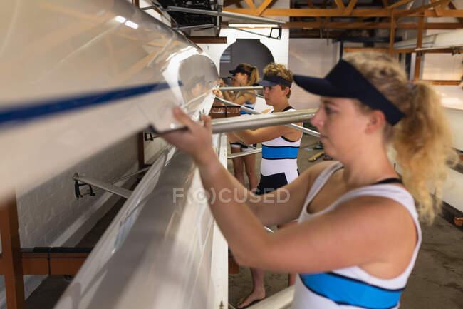 Вид сбоку на команду гребцов кавказских женщин, готовящихся к гребле на гоночной раковине на реке, поднимающих лодку вместе, чтобы вытащить ее из лодочного сарая, избирательный фокус — стоковое фото