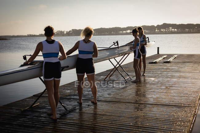 Rückansicht eines Ruderteams von vier kaukasischen Frauen, die auf dem Fluss trainieren, bei Sonnenaufgang auf einem Steg stehen, ein Boot auf Ständer stellen und es für das Rudertraining vorbereiten — Stockfoto