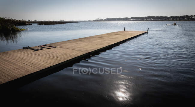 Vista laterale di un molo su un fiume al sole, con la luce del sole riflessa sulle increspature in primo piano — Foto stock