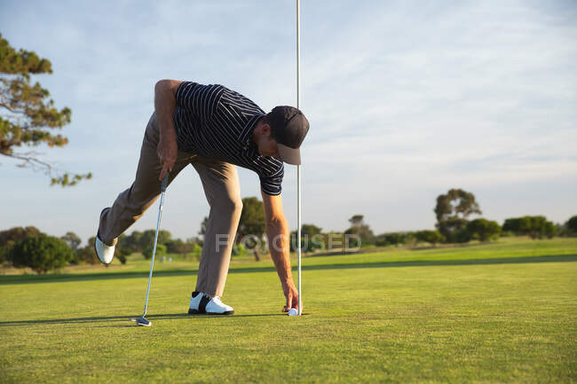 Side view of a Caucasian man at a golf course on a sunny day, placing a golf ball on the grass — Stock Photo