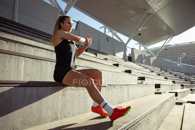 Seitenansicht einer kaukasischen Athletin beim Training in einem Sportstadion, die sich an einem Stand dehnt. — Stockfoto