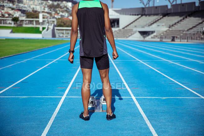 Вид спереди на спортсмена смешанной расы, практикующего на спортивном стадионе, стоящего за стартовыми блоками, сфокусированного перед гонкой — стоковое фото