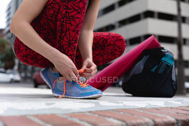 Front view low section of a fit woman on her way to fitness training on a cloudy day, with a sports bag and a yoga mat, kneeling down in the street and tying her shoelaces — Stock Photo