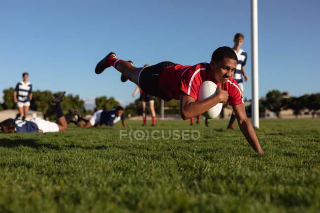 Vue latérale d'un adolescent joueur de rugby mixte portant une bande rouge, sur un terrain de jeu, plongeant avec la balle pour marquer un essai pendant un match, avec des joueurs de l'équipe adverse en arrière-plan — Photo de stock