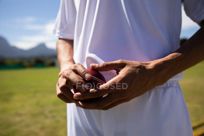 Front view mid section of male cricket player wearing whites, standing on the pitch, holding a cricket ball in hands. — Stock Photo