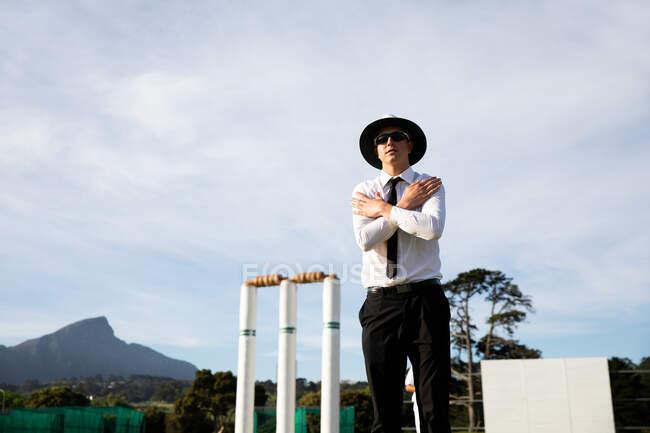 Боковой низкоугольный вид на кавказского судью по крикету в белой рубашке, черном галстуке, широкополой шляпе и солнечных очках, стоящего на поле для крикета у калитки, скрещивая руки. — стоковое фото