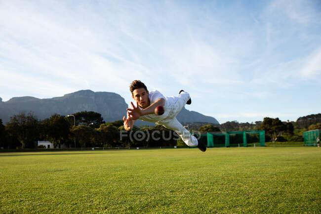 Vue de face d'un adolescent asiatique joueur de cricket portant des blancs, plongeant en essayant d'attraper un ballon de cricket sur le terrain pendant une journée ensoleillée — Photo de stock