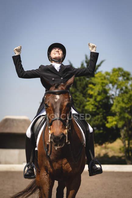 Вид спереди на ловко одетую кавказскую всадницу, сидящую на каштановом коне в загоне, поднимающую руки и улыбающуюся на праздновании во время соревнований по выездке в солнечный день. — стоковое фото