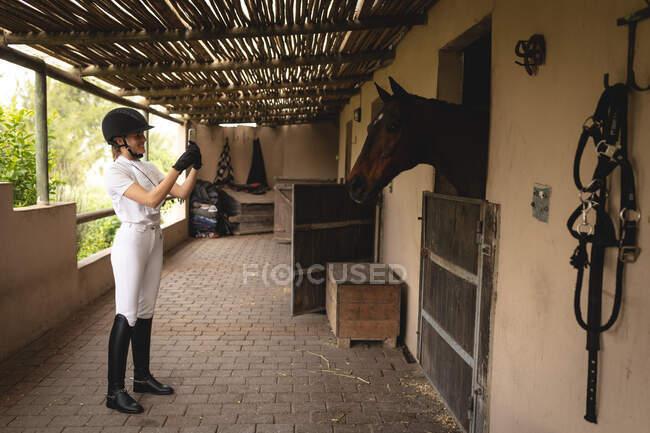 Бічний погляд на одягненого кавказького вершника, який користується своїм смартфоном і фотографує її, а її каштановий кінь стоїть у стайні.. — стокове фото