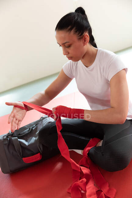 Передній вигляд, закритий підлітком змішаної раси самка дзюдока, сидить на спортзалі матів, обгортаючи червону стрічку навколо її зап'ястка. — стокове фото