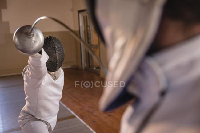 Desportista afro-americana vestindo roupa de esgrima protetora durante uma sessão de treinamento de esgrima, atacando seu oponente com epee bending. Treinamento de esgrimistas no ginásio. — Fotografia de Stock