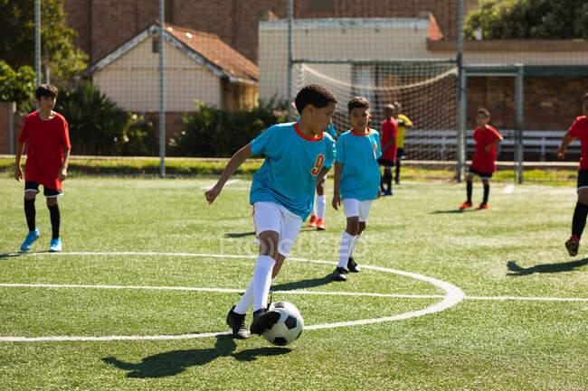Вид сбоку на две многонациональные команды мальчиков-футболистов, одетых в командные костюмы, в действии во время футбольного матча на футбольном поле на солнце — стоковое фото