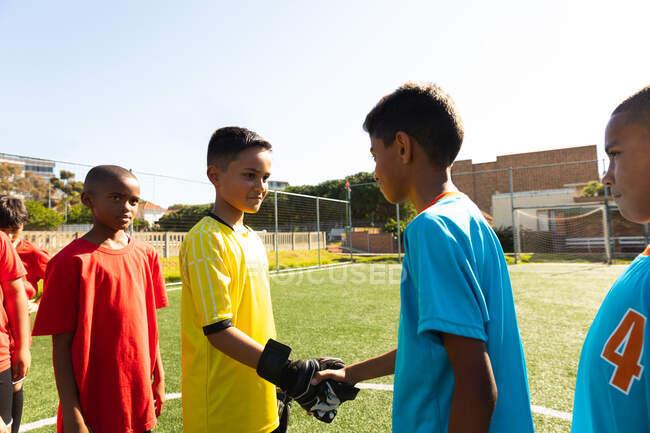 Вид сбоку на многонациональную группу мальчиков-футболистов в командных полосах, пожимающих руку перед футбольным матчем на игровом поле в солнечный день — стоковое фото