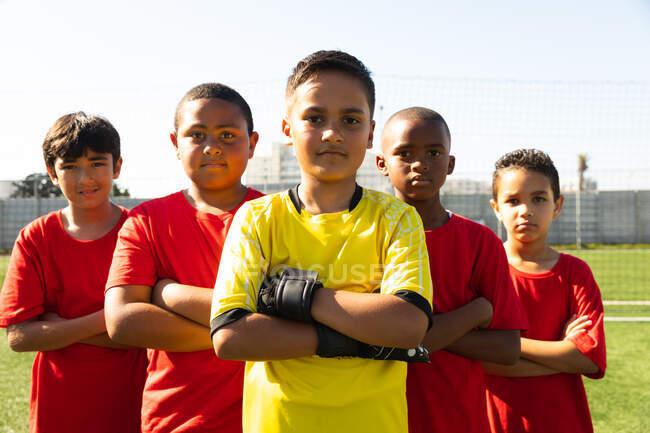 Вид спереди на группу молодых мультиэтнических футболистов в командном раздевании, стоящих на игровом поле со скрещенными руками — стоковое фото