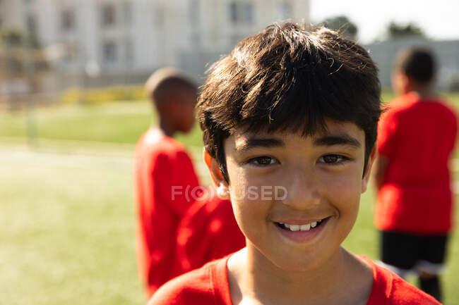 Портрет футболиста смешанной расы, одетого в свою команду, стоящего на игровом поле на солнце, смотрящего в камеру и улыбающегося, с товарищами по команде, стоящими на заднем плане — стоковое фото