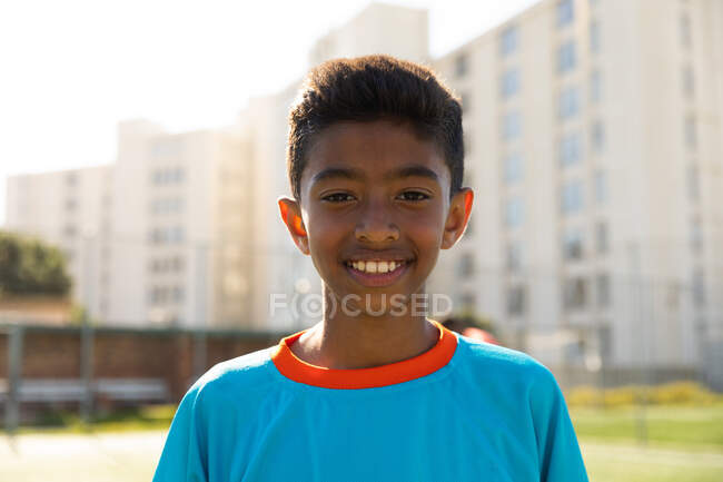 Портрет футболиста смешанной расы, одетого в синюю командную одежду, стоящего на игровом поле на солнце, смотрящего в камеру и улыбающегося — стоковое фото
