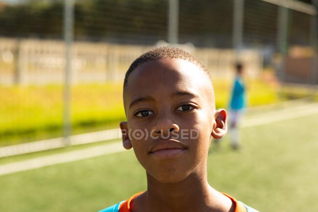 Portrait of a mixed race boy soccer player wearing team strip, standing on a playing field, looking to camera and smiling, with teammates playing in the background — Stock Photo