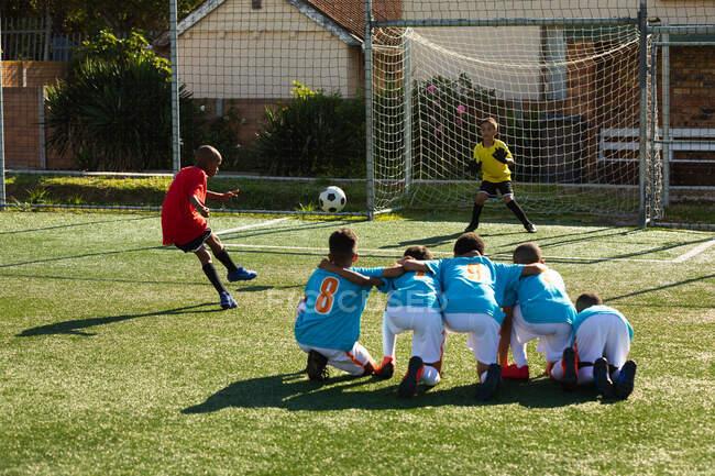 Вид сзади на многонациональную группу мальчиков-футболистов, одетых в командные костюмы, в действии во время футбольного матча на игровом поле на солнце, один мальчик из Африки Америки забил гол — стоковое фото