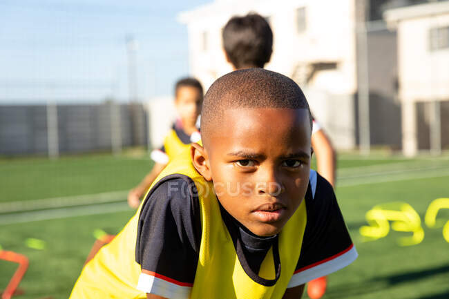 Portrait close up of an African American boy soccer player standing on a playing field on a sunny day, having a rest during training and looking to camera, with teammates in the background — Stock Photo