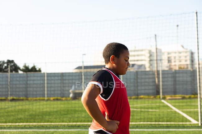 Vista lateral de um jovem jogador de futebol de raça mista em pé em um campo de jogo ao sol, com as mãos nos quadris, tendo um descanso durante o treinamento de futebol — Fotografia de Stock