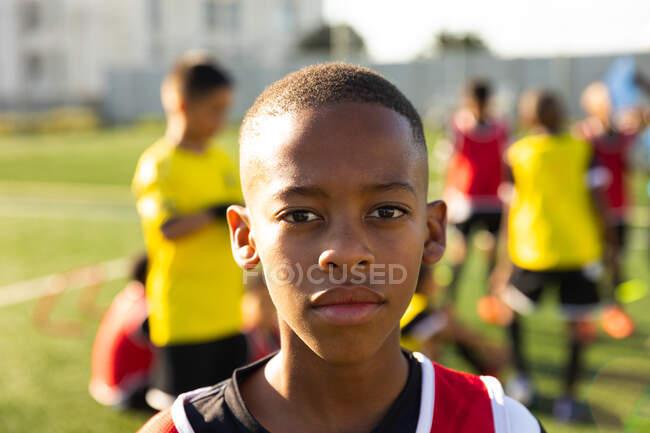 Портрет молодого афроамериканского футболиста, стоящего на игровом поле на солнце во время тренировки, смотрящего в камеру, с товарищами по команде, стоящими на заднем плане — стоковое фото