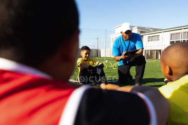 Vista frontal de um treinador misto de futebol masculino ajoelhado e instruindo um grupo multi-étnico de jogadores de futebol sentados em um campo de jogo ao sol durante uma sessão de treinamento de futebol — Fotografia de Stock
