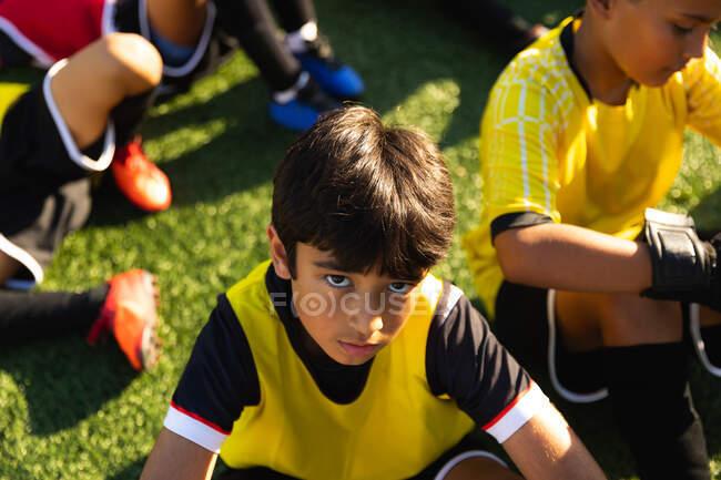 Высокоугловой портрет молодого футболиста смешанной расы, сидящего на игровом поле на солнце и смотрящего в камеру, во время тренировки по футболу, со своими товарищами по команде, сидящими на заднем плане — стоковое фото