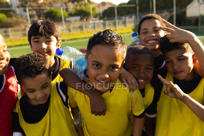 Vue de face d'un groupe multi-ethnique de joueurs de soccer se tenant dans un câlin sur un terrain de jeu au soleil, s'embrassant et regardant vers la caméra, s'amusant, souriant et faisant des gestes lors d'une séance d'entraînement — Photo de stock
