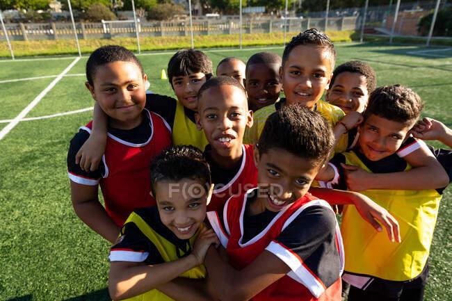Вид спереди на многонациональную группу мальчиков-футболистов, стоящих в куче на игровом поле на солнце, обнимающих друг друга и смотрящих в камеру улыбающихся во время тренировки — стоковое фото
