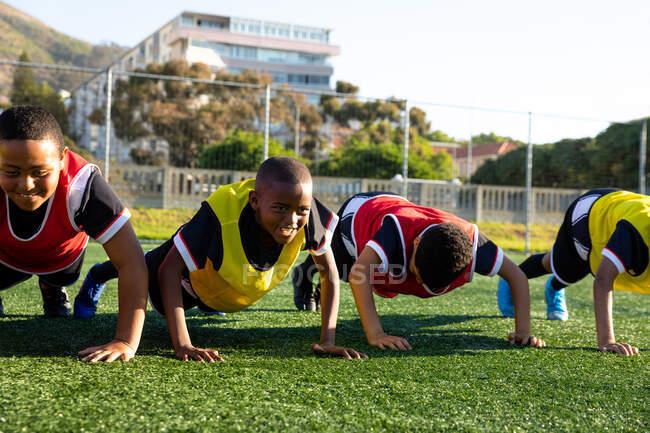 Vue de face gros plan d'un groupe multiethnique de garçons joueurs de soccer faisant des reportages consécutifs sur un terrain de jeu au soleil lors d'une séance d'entraînement de soccer — Photo de stock