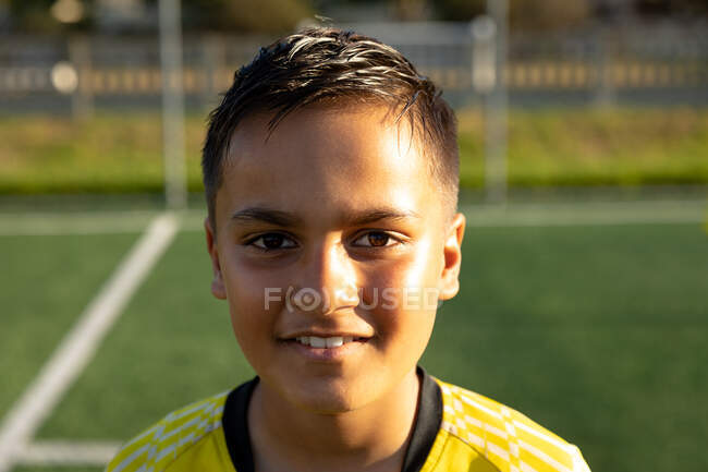 Portrait close up of a confident mixed race boy soccer player wearing a team strip, standing on a playing field in the sun, looking to camera and smiling — Stock Photo