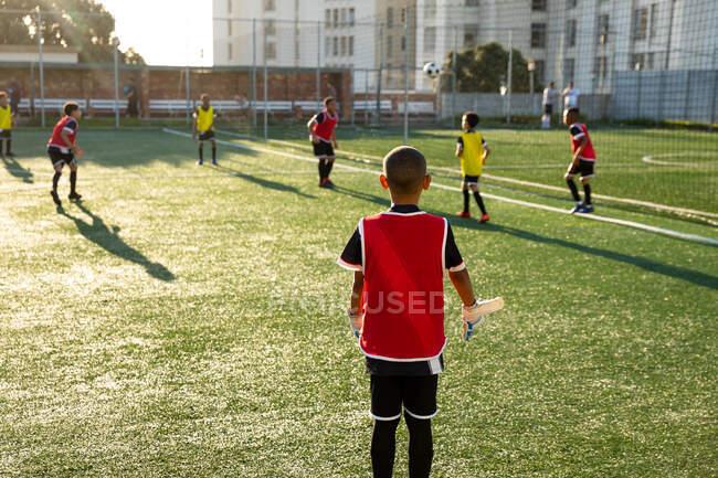 Vue arrière d'un groupe multiethnique de garçons joueurs de soccer en action sur un terrain de jeu, donnant un coup de pied au ballon lors d'une séance d'entraînement de soccer — Photo de stock