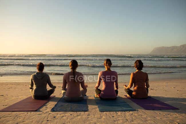 Rückansicht einer multiethnischen Gruppe von Freundinnen, die an einem sonnigen Tag am Strand Sport treiben, Yoga im Sitzen praktizieren und meditieren, mit Blick auf das Meer. — Stockfoto