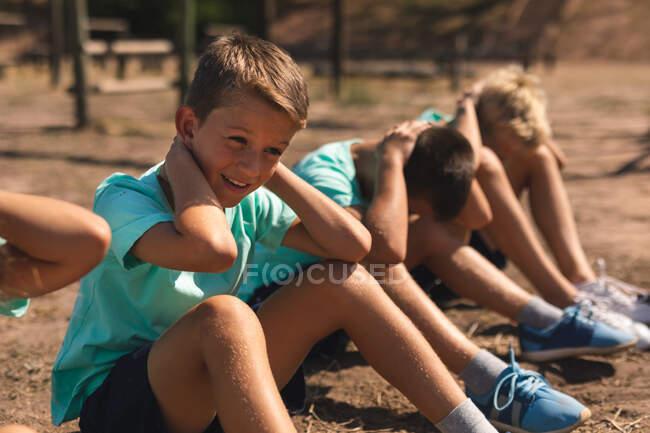 Группа кавказских мальчиков в учебном лагере в солнечный день, сидящих в ряд и хрустящих, или сидящих, все в зеленых футболках и черных шортах — стоковое фото