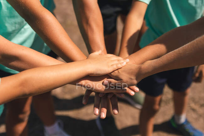 Mid section of a group of boys and girls at a boot camp on a sunny day, bonding and stacking hands together before doing an obstacle course, all wearing green t shirts and black shorts — Stock Photo