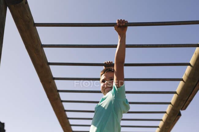 Garçon caucasien souriant aux cheveux bruns dans un camp d'entraînement par une journée ensoleillée, portant un t-shirt vert, sur une salle de gym de jungle suspendue aux barres de singe contre un ciel bleu — Photo de stock