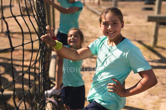 Портрет белой девушки в учебном лагере в солнечный день, держащейся за сетку на скалолазании и улыбающейся в камеру, одетой в повязку, зеленую футболку и черные шорты, с детьми на заднем плане — стоковое фото