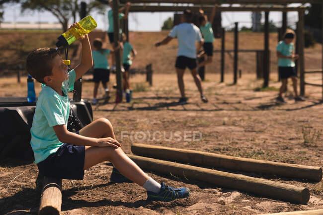 Garçon caucasien à un camp de démarrage par une journée ensoleillée, assis sur une bûche et verser de l'eau d'une bouteille d'eau sur sa tête pour se rafraîchir, avec un entraîneur masculin et d'autres enfants travaillant en arrière-plan — Photo de stock