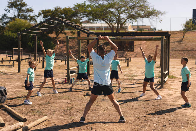 Rear view of Caucasian male fitness coach instructing a group of Caucasian boys girls at a boot camp on a sunny day doing jumping jacks wearing green t shirts and black shorts — Stock Photo